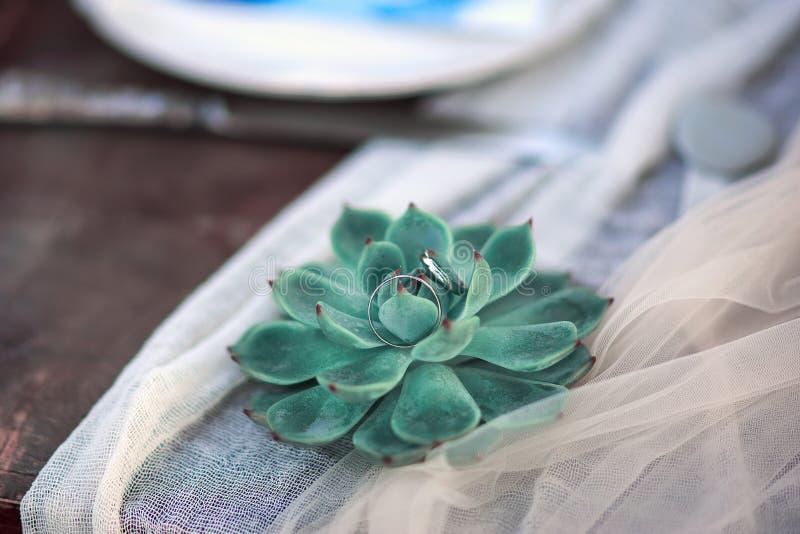 Красивый деревенский цветок стиля свадьбы с кольцами свадьбы золотыми на белой ткани на деревянном столе стоковые фото