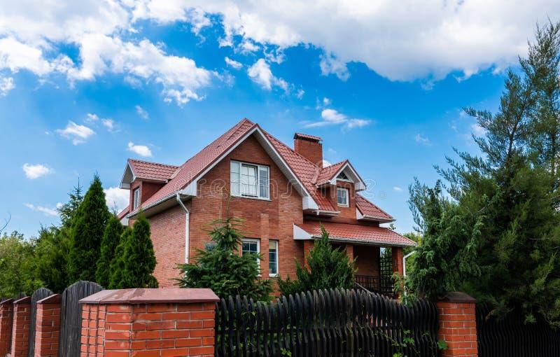 Красивый дом красного кирпича на предпосылке голубого неба, загородный дом стоковые фото