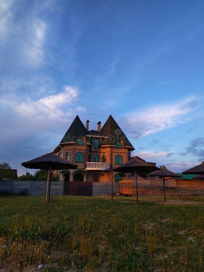 Красивый дом на заходе солнца, облачное небо, естественная предпосылка стоковая фотография rf