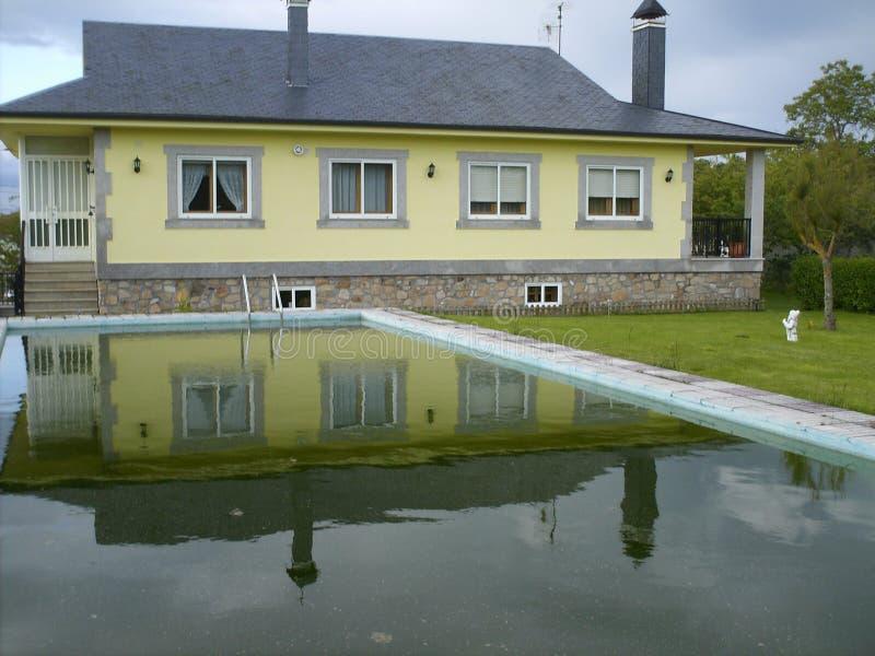 Красивый желтый дом семьи с бассейном и садом стоковое изображение