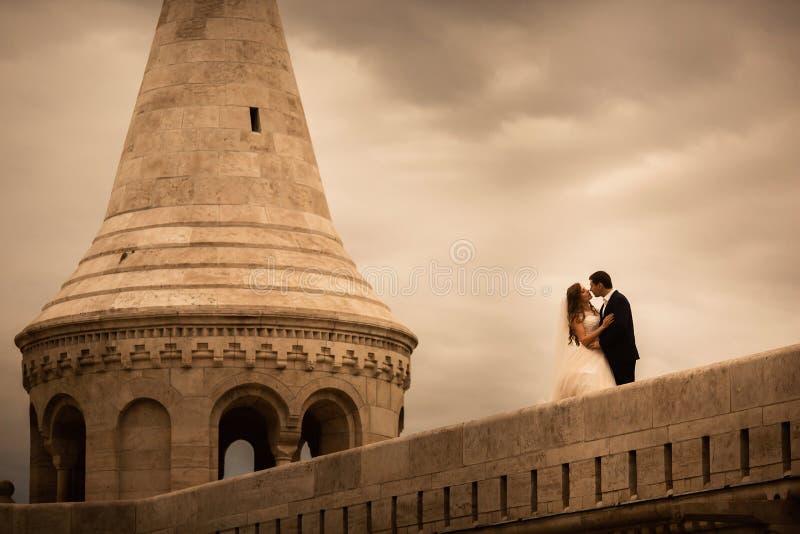 Красивый жених и невеста обнимая и целуя на их день свадьбы в старом городе стоковая фотография rf