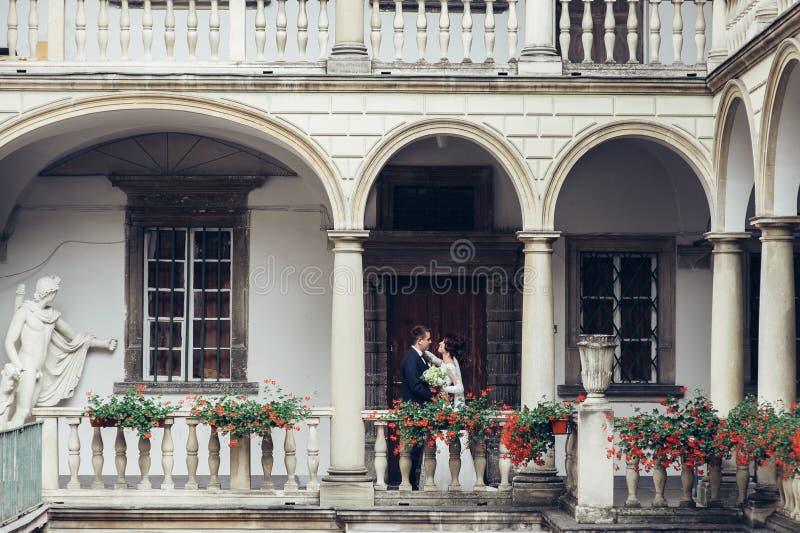 Красивый жених и невеста обнимая и целуя на их свадьбе стоковая фотография