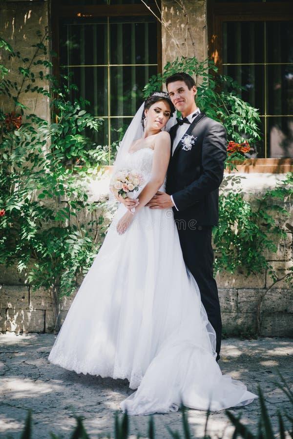 Красивый жених и невеста представляя в дворе замка стоковые фото
