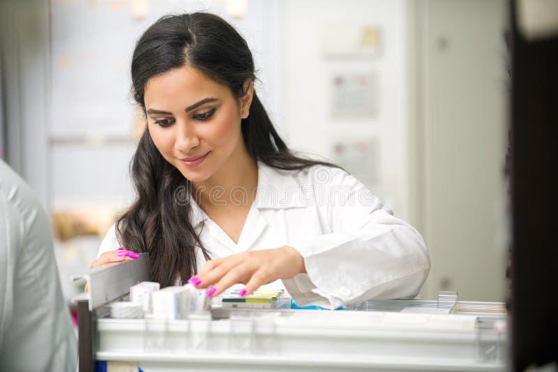 Красивый женский аптекарь смотря медицину стоковые фотографии rf