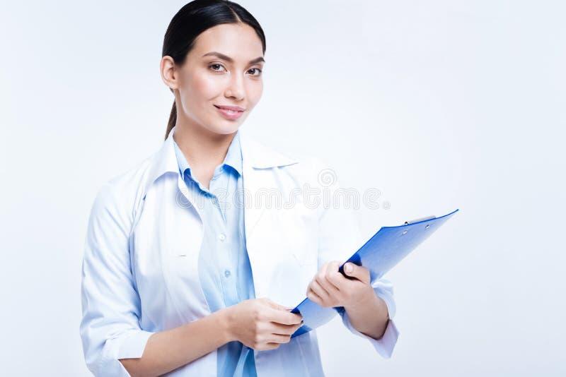 Красивый женский доктор представляя с держателем h листа стоковая фотография rf