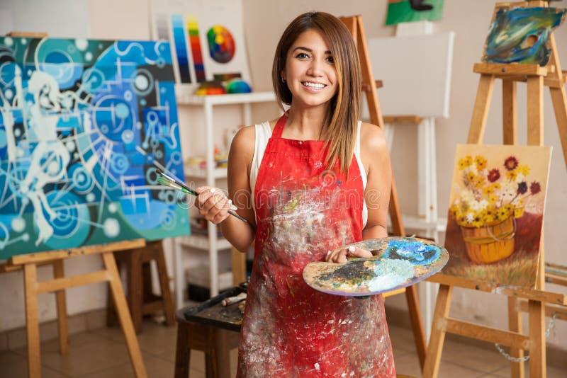 Красивый женский художник в ее студии стоковая фотография