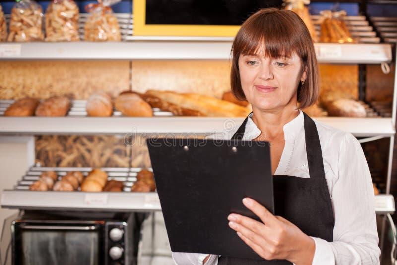 Красивый женский хлебопек подготавливает для ее работы стоковые изображения