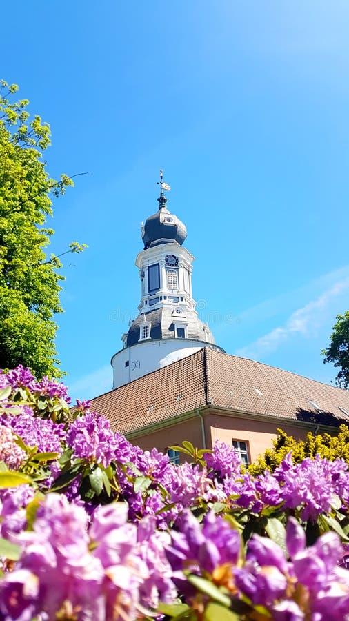 Красивый замок в Jever с розовым рододендроном стоковая фотография