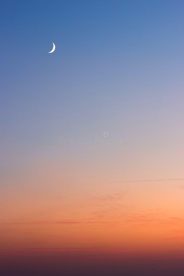 Красивый заход солнца лета - темно-синее небо с видимой луной и оранжевым горизонтом стоковое фото