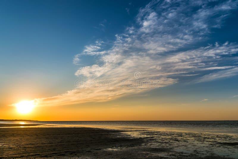 Красивый заход солнца над берегом моря при облака достигая горизонт стоковое фото rf
