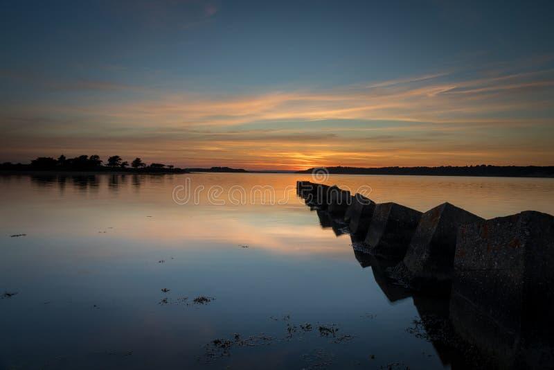 Красивый заход солнца над заливом с отражениями на барьере стоковые изображения rf
