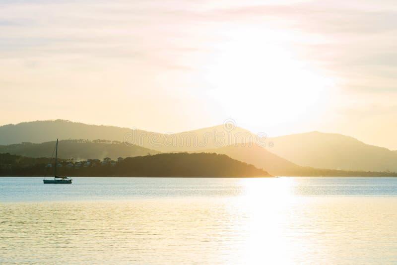 Красивый заход солнца над морем и тропическим пляжем в временени с стоковые изображения