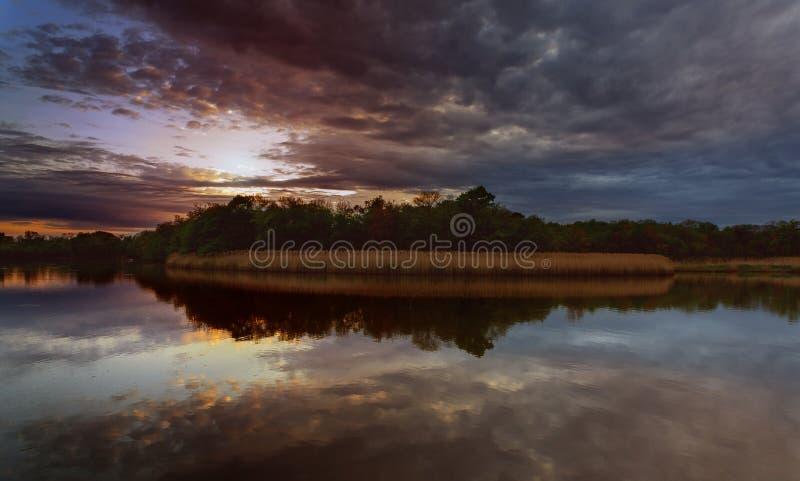 Красивый заход солнца над озером с отражением в воде, величественные облака в тонизированном небе отображает стоковое фото