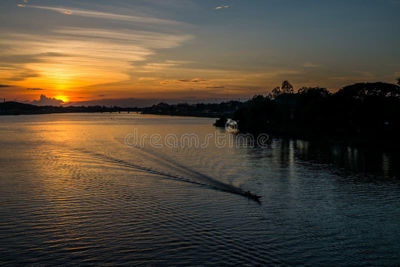 Красивый заход солнца отразил с шлюпкой в реке, Таиланде стоковая фотография