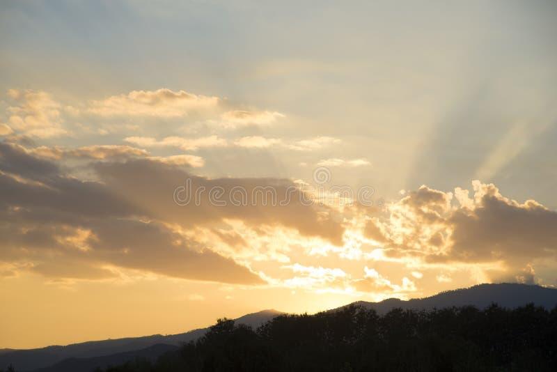 Красивый заход солнца с оранжевым солнечным светом, ландшафтом горы под небом облака, обоями захода солнца безмятежности стоковое фото rf