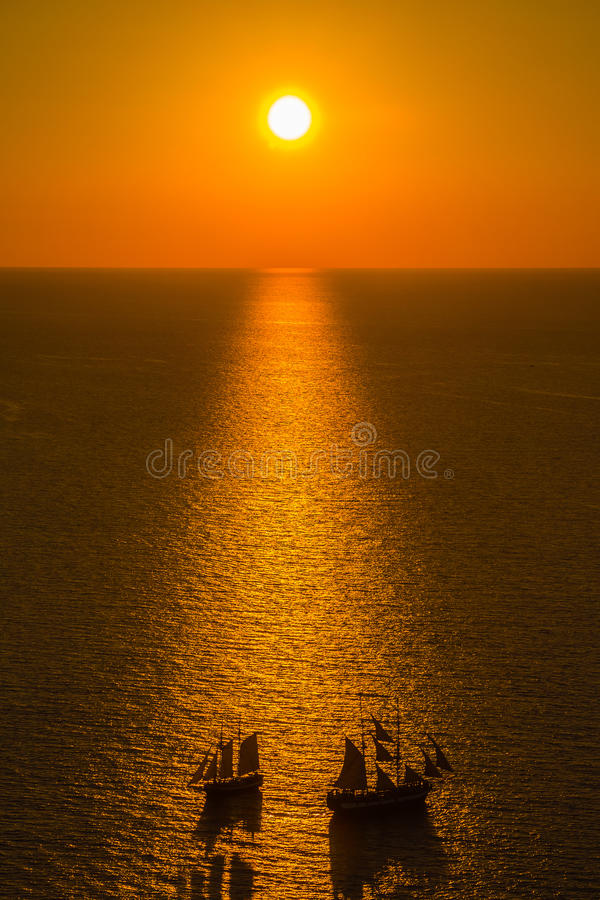 Красивый заход солнца над кальдерой при 2 шлюпки пересекая, Oia Santorini, Santorini, Грецией стоковая фотография rf