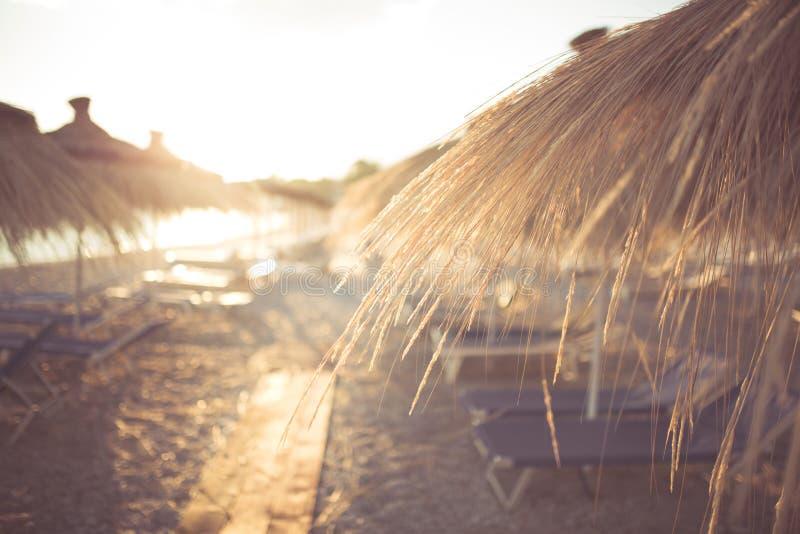 Красивый заход солнца на красивом песчаном пляже с навесами стоковое изображение rf