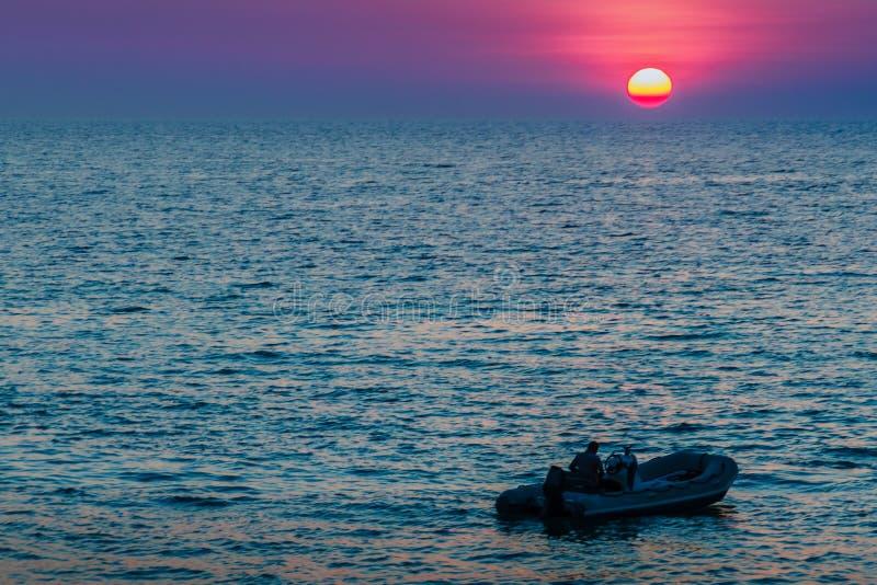 Красивый заход солнца на море с апельсином, кругом и ярким солнцем дальше стоковые фото