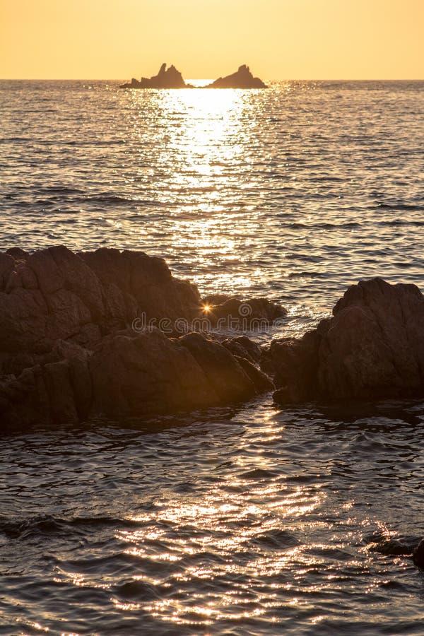 Красивый заход солнца над скалистым seashore стоковое изображение