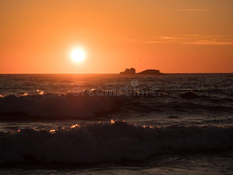 Красивый золотой заход солнца на океане с волнами в переднем плане стоковое изображение
