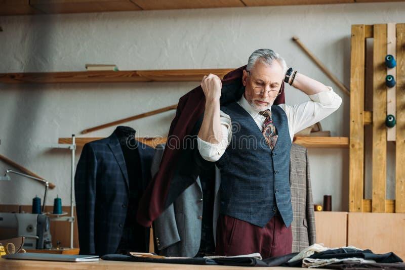 красивый зрелый портной кладя куртку на плечи стоковое фото rf