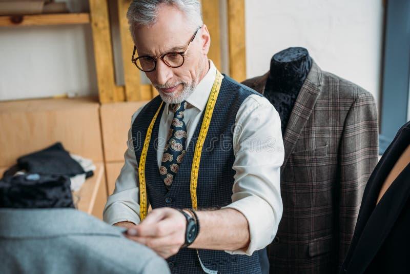 красивый зрелый портной с измеряя лентой смотря куртку на манекене стоковое изображение rf