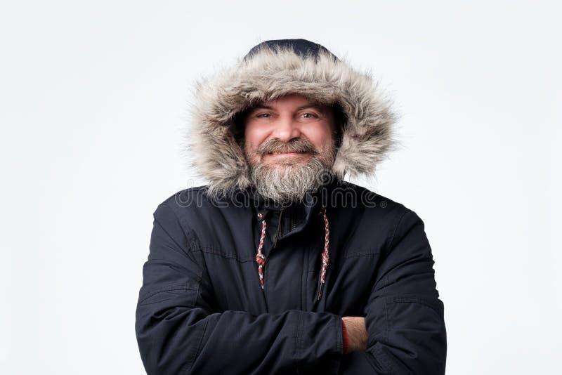 Красивый зрелый человек нося теплый parka и клобук зимы, усмехаясь стоковое изображение