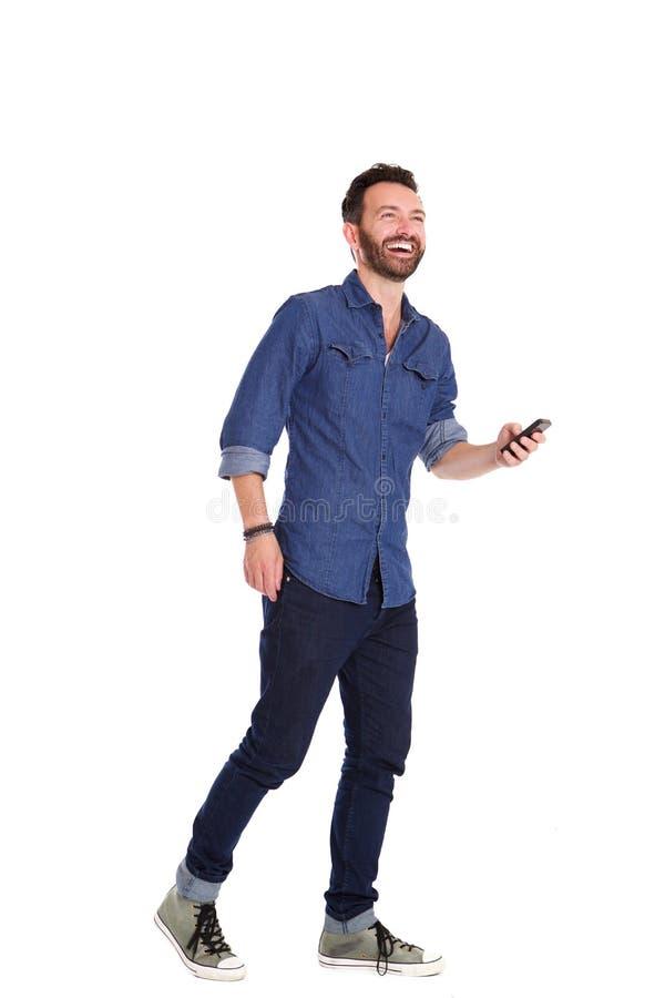Красивый зрелый человек идя с мобильным телефоном и смеяться над стоковое изображение rf