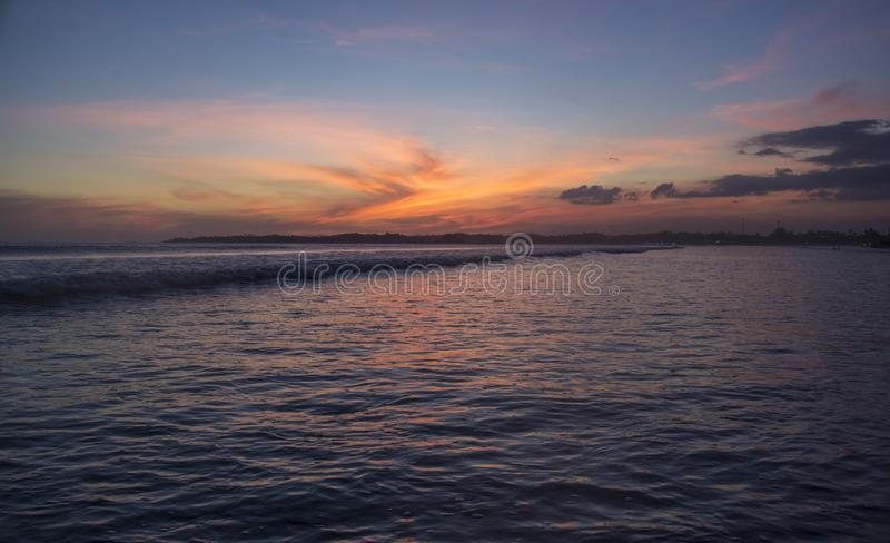 Красивый изумительный ландшафт тропического пляжа под оранжевым небом захода солнца стоковые изображения