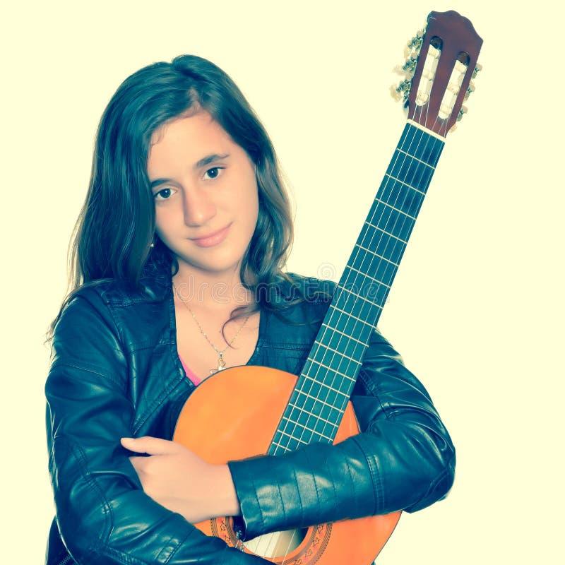 Красивый испанский девочка-подросток обнимая ее акустическую гитару стоковое изображение