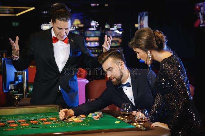 Красивый и богатый человек играя рулетку в казино стоковое фото
