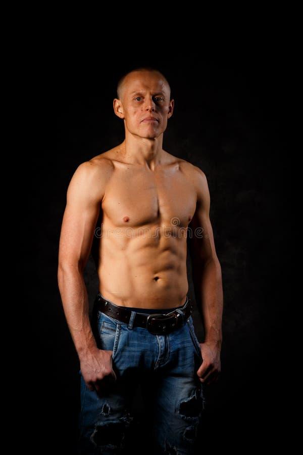 Красивый и мышечный человек в темной предпосылке стоковая фотография rf