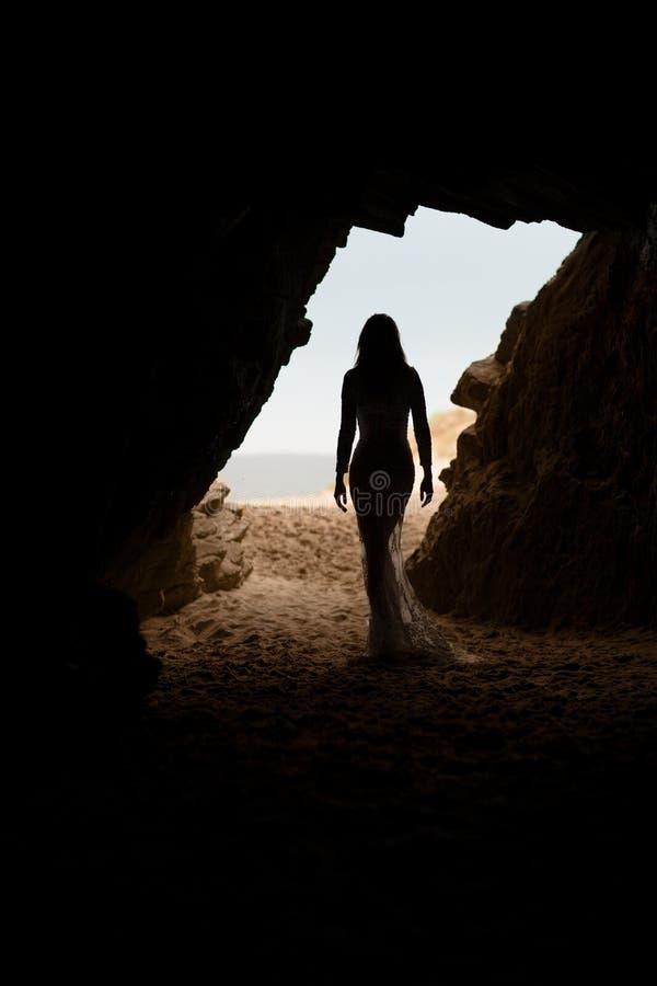 Красивый и сексуальный силуэт тела женщины в длинном платье в пещере стоковые фотографии rf