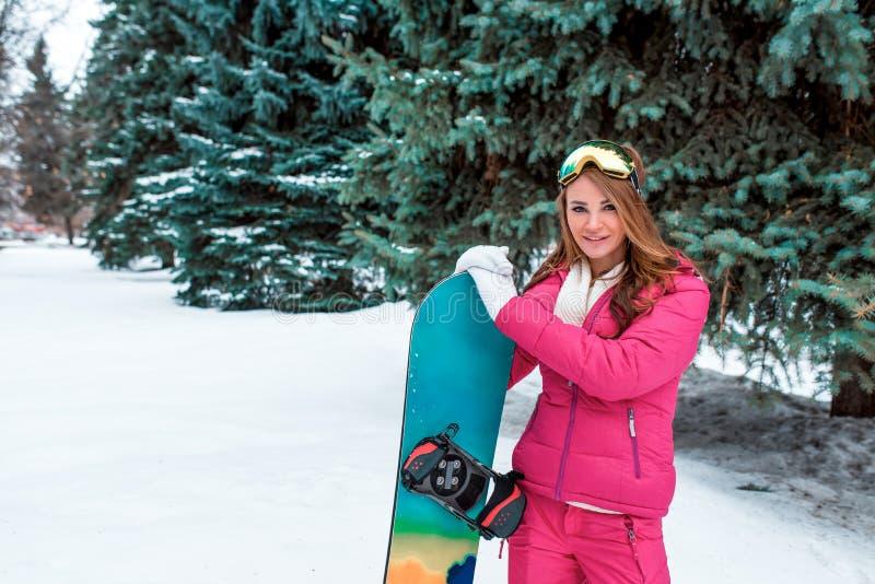 Красивый и счастливый лес зимы девушки оно сноубординг стоимости, маска предохранения от солнца Счастливая усмехаясь ель снега фо стоковые изображения rf