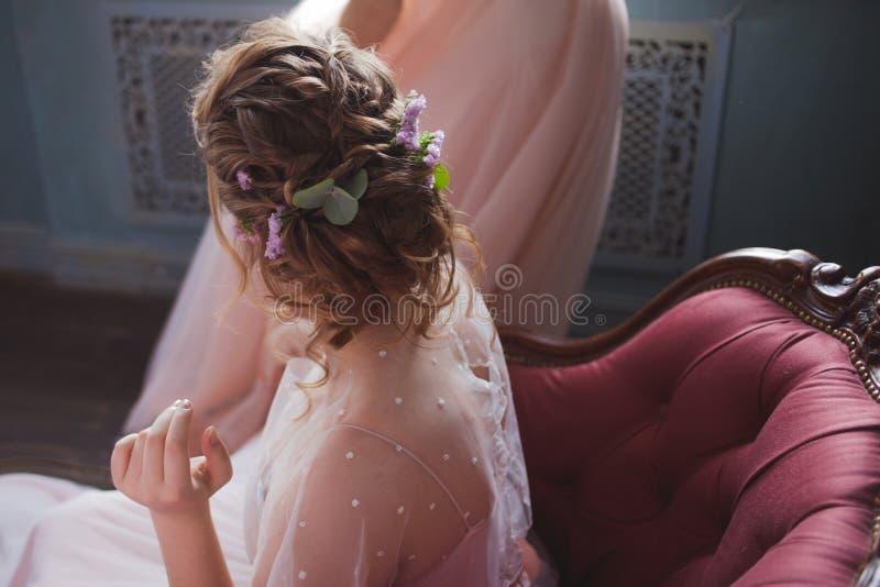 Красивый и элегантный стиль причесок свадьбы Молодая невеста сидя в стуле стоковое изображение rf