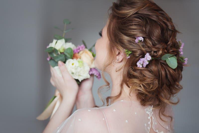 Красивый и элегантный стиль причесок свадьбы Молодая невеста с букетом цветков стоковое фото