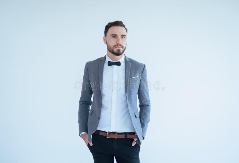 Красивый кавказский человек с бородой в официальном положении смокинга и костюма и усмехаться на белой предпосылке, копирует косм стоковая фотография rf