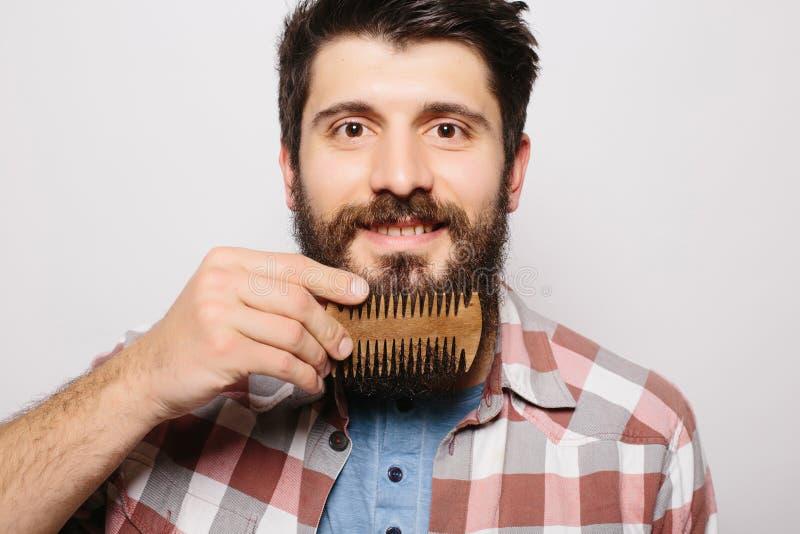 Красивый кавказский человек с смешной улыбкой усика и расчесывает его большую бороду стоковое фото