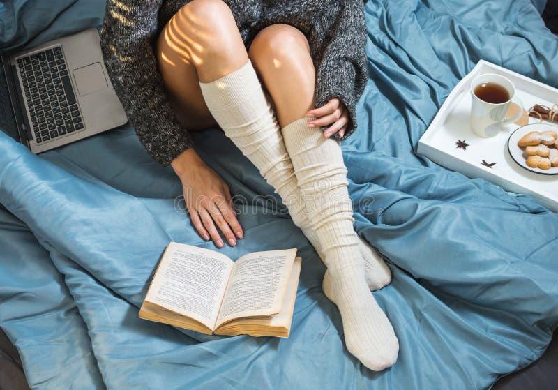 Красивый конец-вверх ног в кровати, девушке с чашкой чаю и читать книгу стоковые фото