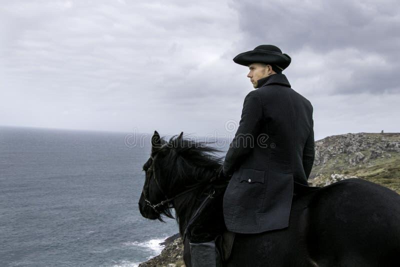 Красивый костюм Poldark XVIII века регентства всадника мужской лошади с руинами шахты олова и Атлантический океан в предпосылке стоковые изображения