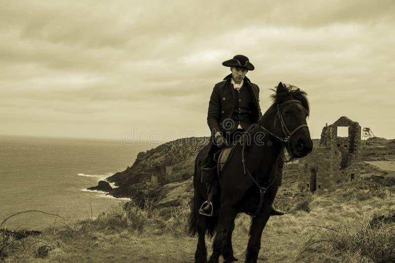 Красивый костюм Poldark XVIII века регентства всадника мужской лошади с руинами шахты олова и Атлантический океан в предпосылке стоковое фото rf