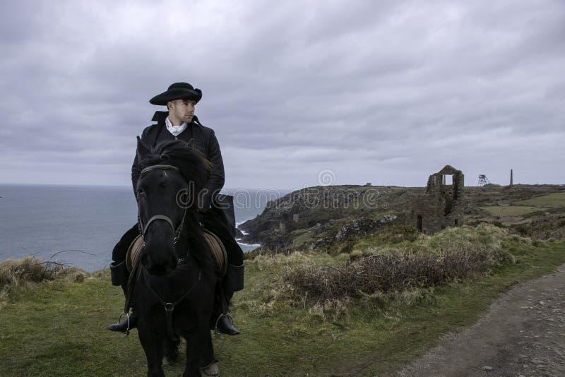 Красивый костюм Poldark XVIII века регентства всадника мужской лошади с руинами шахты олова и Атлантический океан в предпосылке стоковые фото