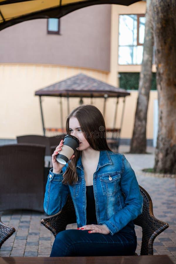 Красивый кофе напитка девушки в кафе outdoors стоковые изображения