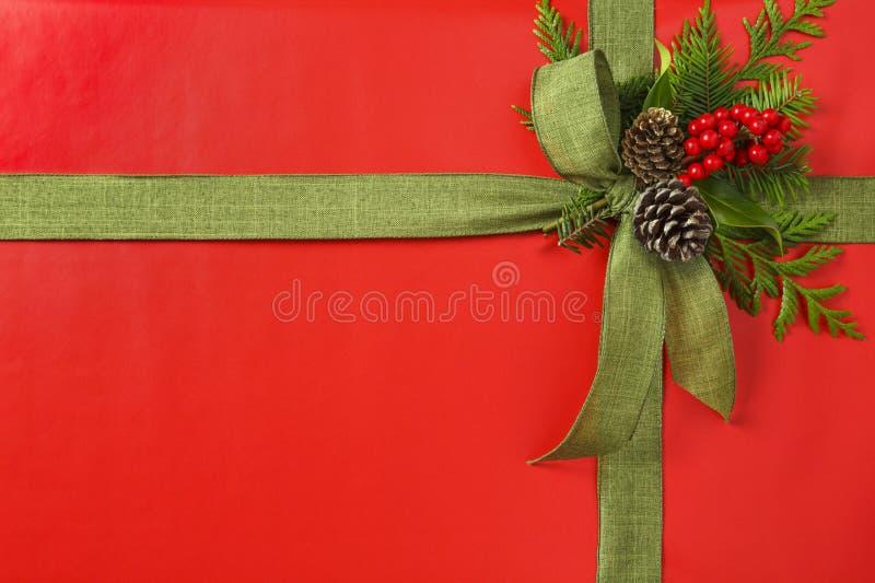 Красивый красный и зеленый подарок рождества присутствующий с смычком ленты ткани и ботаническими украшениями Горизонтальная гран стоковые изображения rf