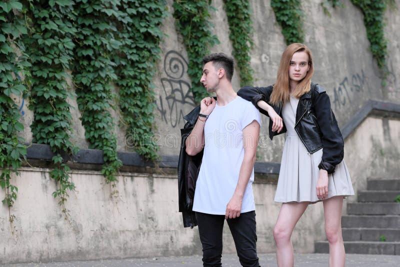 Красивый красный с волосами парень девушки и брюнет представляя совместно стоковое изображение