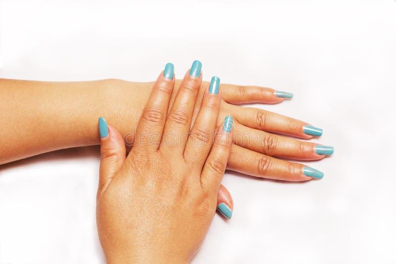 Красивый крупный план рук молодой женщины с длинным голубым маникюром на ногтях стоковое изображение