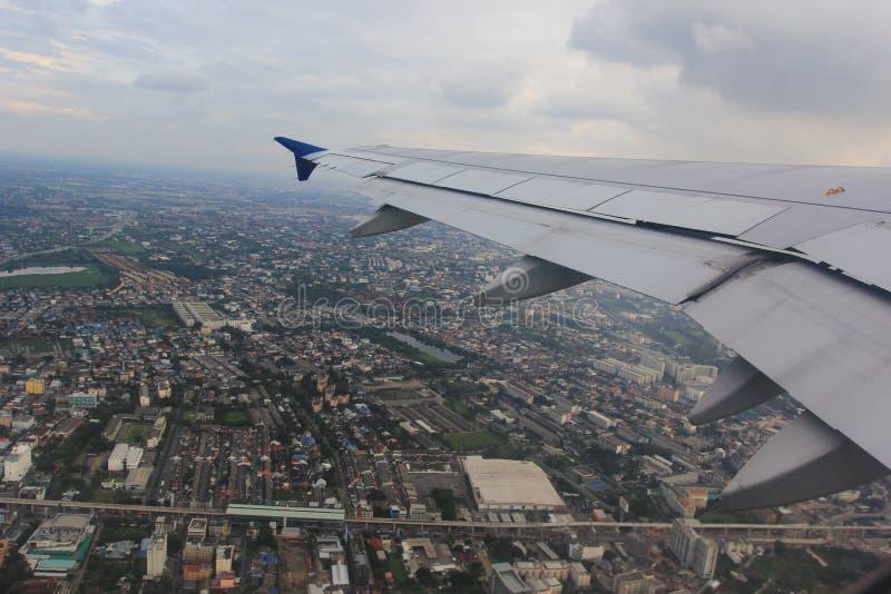 Красивый крыла самолета с городом и голубого неба на заходе солнца стоковое фото