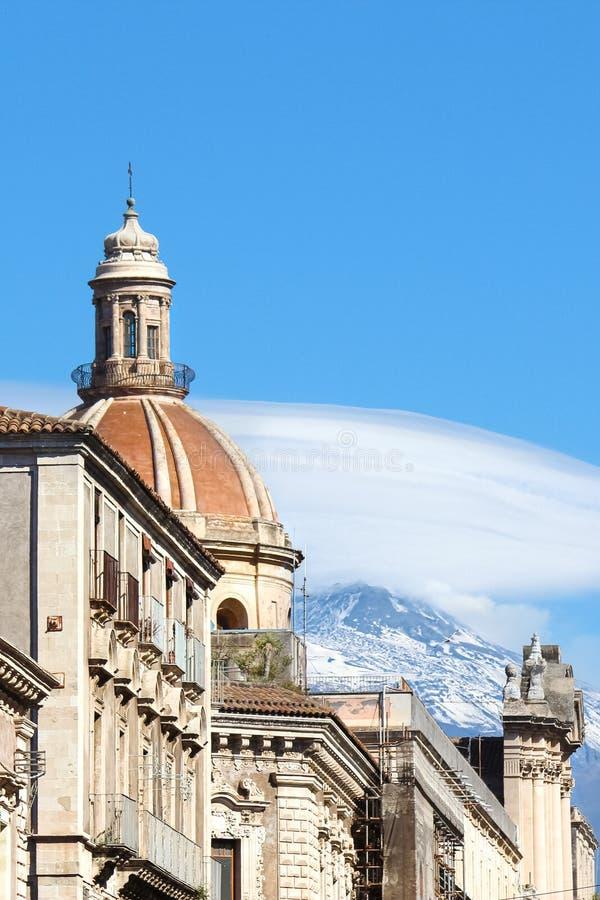 Красивый куполок собора Agatha Святого в Катании, Сицилии, Италии захватил на вертикальном фото с известной горой Этна вулкана стоковые фото