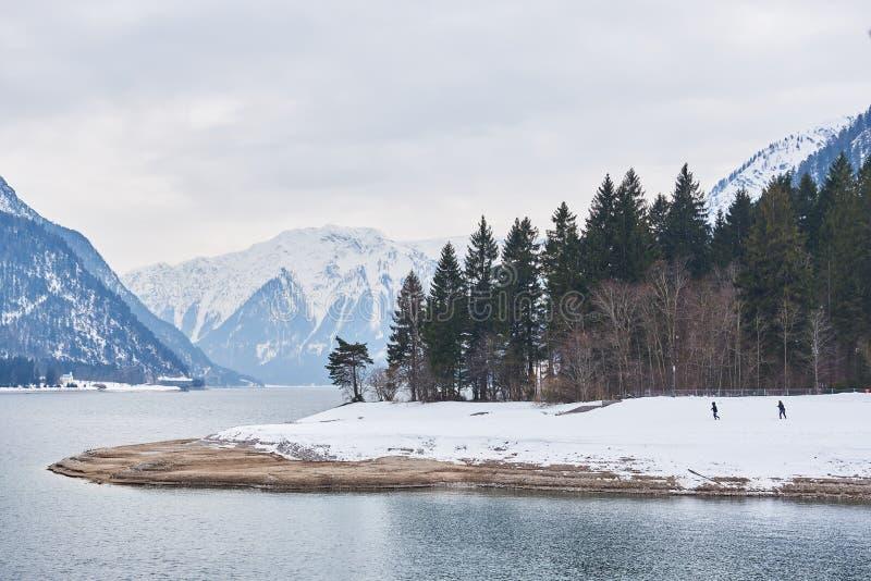 Красивый ландшафт зимы с 2 людьми на Achensee/озере Achen, австрийце Альпах стоковая фотография