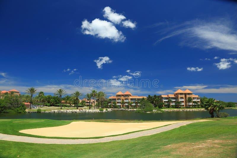 Красивый ландшафт на острове Аруба синь заволакивает белизна неба валы песка гольфа флага поля цветов осени стоковые изображения